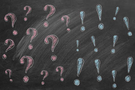 Hand drawn question marks on the left and exclamation marks on the right. Illustration are drawn in chalk on a blackboard. FAQ or discussion concept.