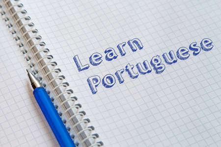 Learn Portuguese. Text handwritten on sheet of notebook