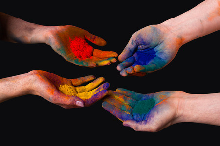 colored powder: Colorful painted hands, holding holi isolated on black