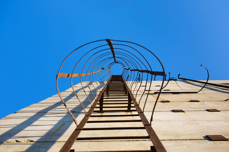 fall arrest: Old vertical industrial metal rusted ladder. Staircase to blue sky with clouds with safety rails and screens landings
