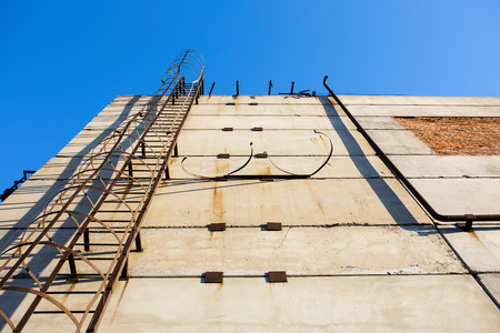 fall arrest: Old vertical industrial metal rusted ladder on the concrete wall. Staircase to blue sky with clouds with safety rails