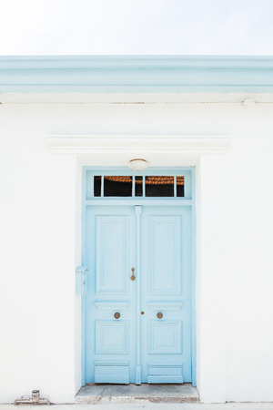 The classical architecture of the Mediterranean (Greece, Italy, Spain, Cyprus, Portugal). Wooden light blue (turquoise) door on the white building. Cyprus, Limassol. photo