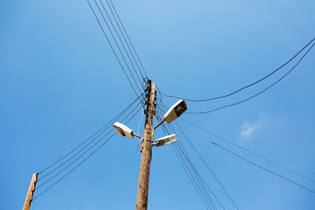 powerline: Powerline on wooden pillar. Electricity poles with a lamp and wires.