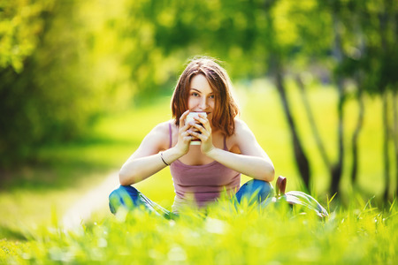 Young woman with takeaway coffee outdoors on sunny summer day. Beautiful girl sitting at the grass in park with beverage. Banco de Imagens
