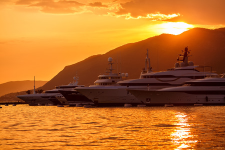 Yachts parking in marina. Mooring yachts and boats. Mountains and sunset background.