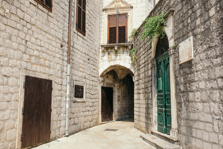 view of a staircase in a shop: KOTOR, MONTENEGRO - AUGUST 2015 : Narrow streets of an old medieval town. UNESCO heritage site.
