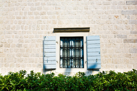 security shutters: Window with Open Wooden Shutters. Decorated with Black Metal Security Bar.