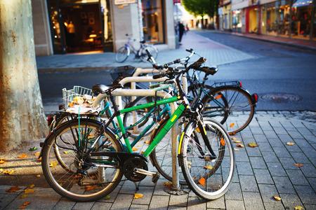 bicicleta: Bicicletas aparcadas en la acera. Estacionamiento de la bici en la calle. Foto de archivo