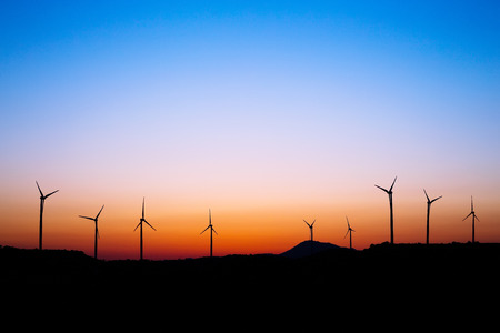 conservation: Wind farm silhouette in sunset light. Stock Photo