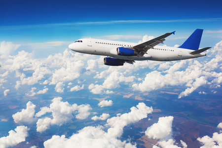 aeroplane: Commercial airliner flying above clouds with blue sky in background.
