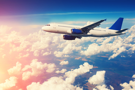 aeroplanes: Commercial airliner flying above clouds with blue sky in background.