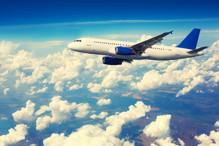 liner transportation: Commercial airliner flying above clouds with blue sky in background.