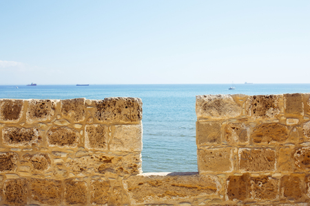 loophole: Limestone fort wall close-up. Sea view.