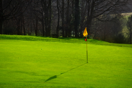 Golf course in the countryside. Green field with a flagstick Banco de Imagens