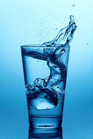 vasos de agua: cubo de hielo cayendo en un vaso de agua