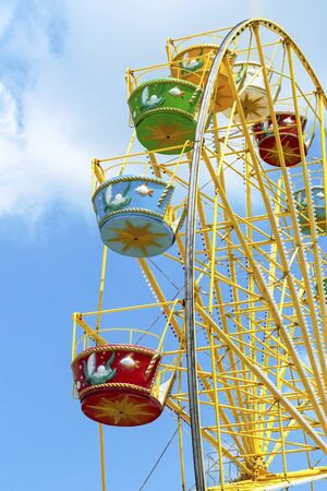 Ferris wheel with colorful colorful booths in the amusement Park against a bright blue sky Stock Photo