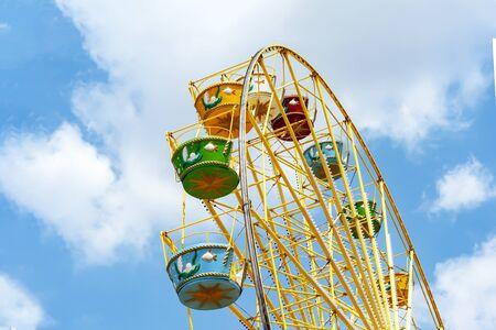 Riesenrad gegen den blauen Himmel. Riesenrad mit bunten bunten Buden im Vergnügungspark