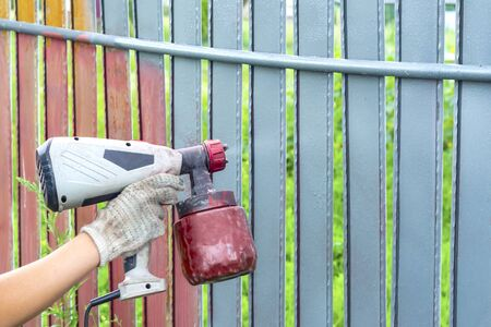 Painting metal fence spray. Man paints a fence with a paint sprayer Imagens