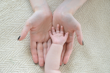 smal: little childs hand in mothers arms