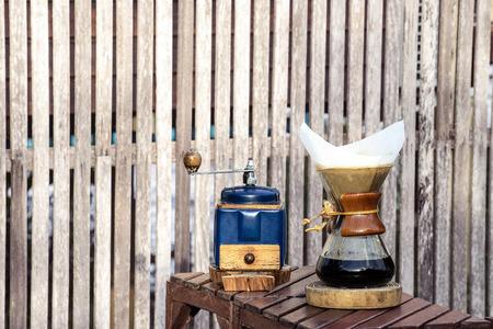papel filtro: molinillo de café de metal y jarra de cristal goteo en fondo de madera vieja