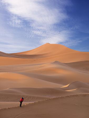 Woman Traveler  looking through camera in sahara desert Фото со стока