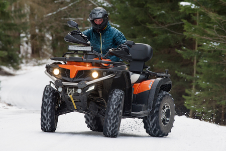 Man driving a quad bike in the winter Stock Photo