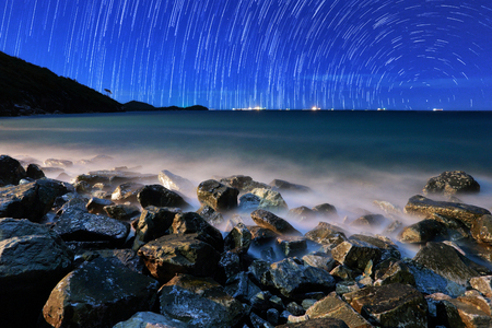 star trail: The motion beautiful star trail image during the night in the sea.