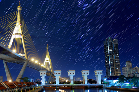 timelapse: The night sky , the stars and the Tallest building in the city. Stock Photo