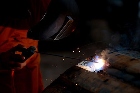 improvisation: Close-up worker with protective mask welding metal.