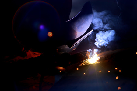 skilled labour: Close-up of welder working in workshop.
