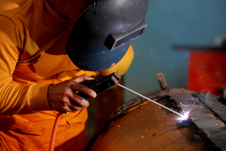 prefabricate: Close-up worker with protective mask welding metal.