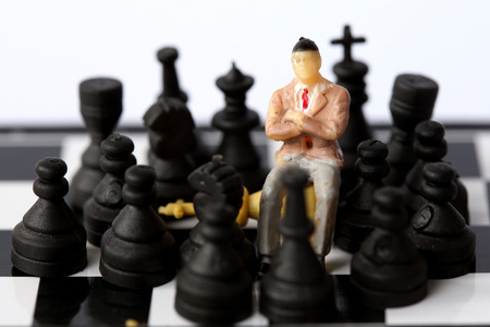 man trapped: Businessman model on chess board.