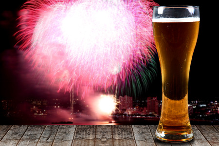 A Glass of beer on wooden background fireworks.Concept Festive Celebrations.