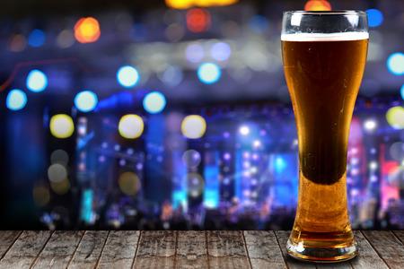 concert lights: Glass of beer on a wooden background concert lights bokeh.Concept Festive Celebrations.