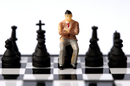 business decisions: Businessman model on chess board.