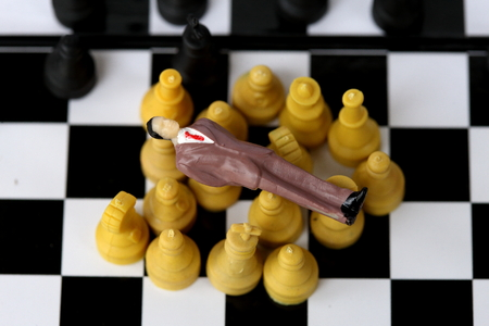 outwit: Businessman model on chess board.