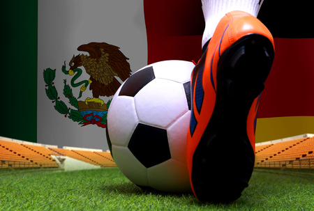 close up legs and feet of soccer player or football player walk on green grass ready to play match on national German and national Mexico. Standard-Bild - 103270054