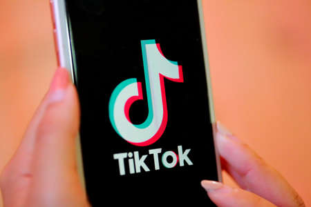 Nakhonratchasima, Thailand - May 31, 2020 : Tik Tok application on iPhone 8, finger about to touch it.which is a popular social media network is app to create and share videos on the internet.