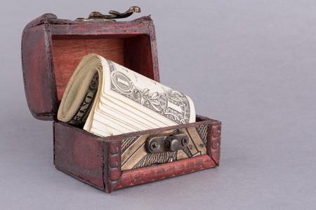 One dollar bills in wooden chest