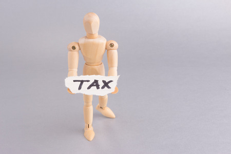TAX word with wooden mannequin