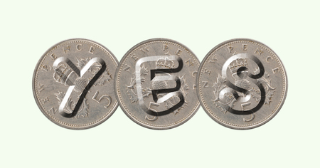 YES written with old British coins on green background