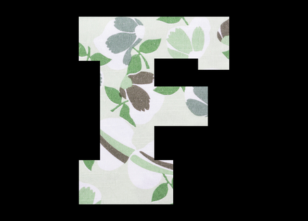 Letter F – with flowery fabric texture on black background 写真素材