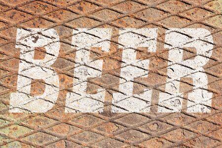 Word BEER on rusty metal texture background