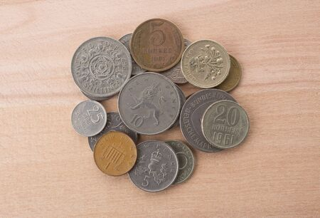 stack of old coins on wooden background.