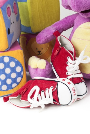 Red and white baby shoes with various toys Stock Photo - 13221110
