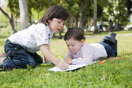 friendship tree: Children painting pictures on the grass in the garden