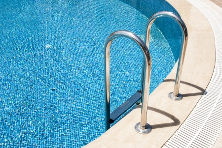 Side of a swimming pool with chrome stairs photo