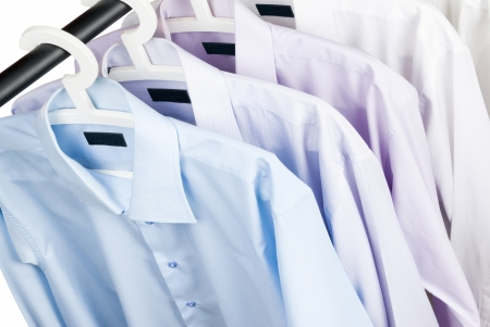 Multicolored shirts on plastic hangers, white background photo