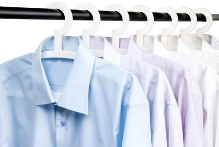 Multicolored shirts on plastic hangers, white background