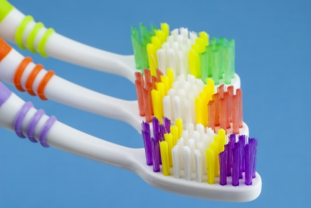 three colorful toothbrushes isolated on blue background 免版税图像